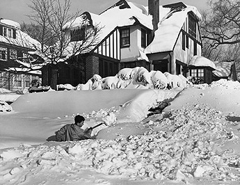 Vintage man doing snow shoveling in front of house.