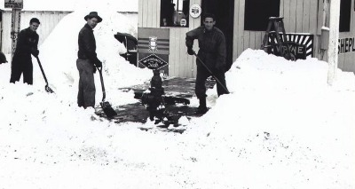 Vintage group of men shoveling snow from sidewalk path.