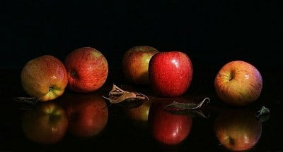 five gala apples on reflective table