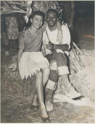 Vintage couple sitting on hay.