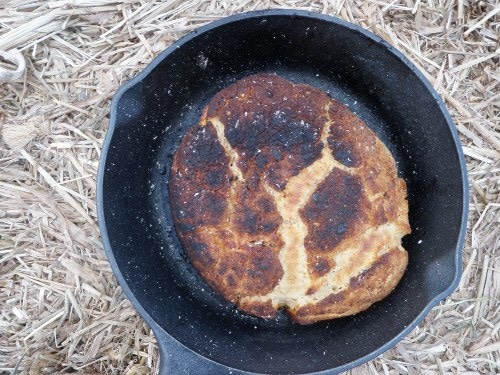 Cooked bannock bread in iron skillet at outdoors.