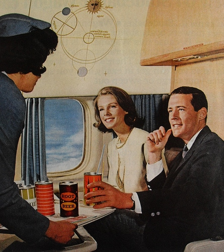 A man serving the drinks to coulple sitting in aeroplane.
