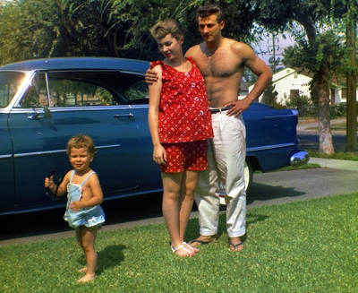 Man standing with his pregnant wife and child in front of car.