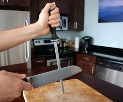 honing sharpening kitchen knife on cutting board