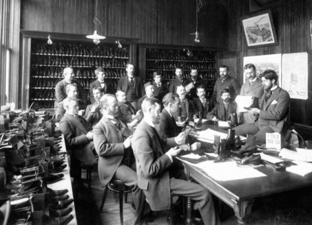 Group of men sitting in shoe store.