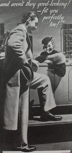 Vintage man showing his shoes to woman sitting in car.