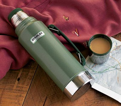 green stanley thermos on table coffee in cup