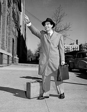 vintage businessman hailing taxi overcoat luggage