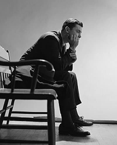 vintage man sitting waiting in chair head on fist