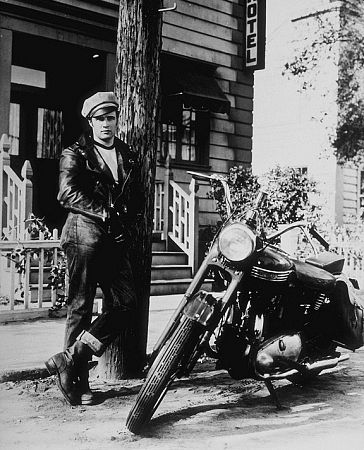 Marlon Brando standing in front of motorcycle.