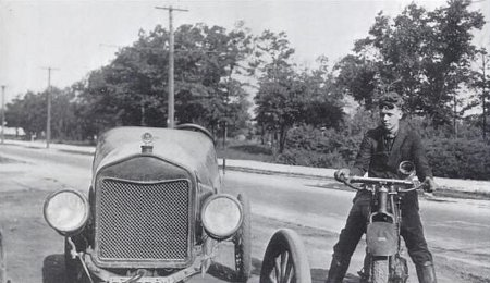 young charles lindbergh on motorcycle next to car