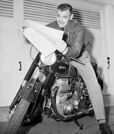 Clark Gable reading newspaper while riding on motorcycle.