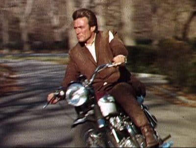 Clint Eastwood riding on motorcycle.