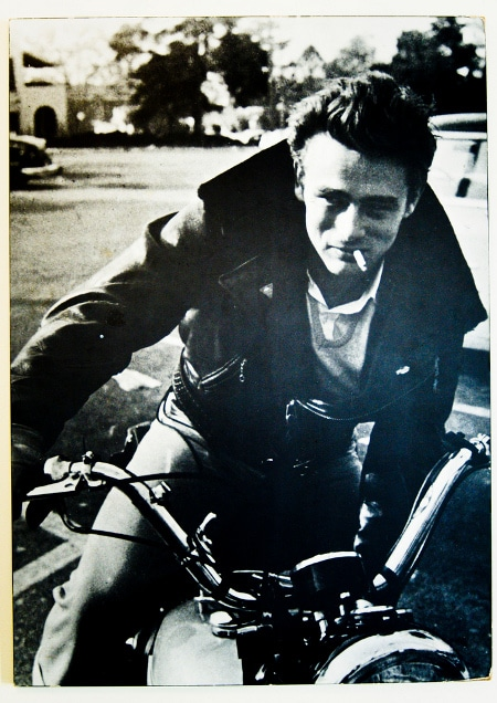 James Dean riding on motorcycle with smoking pose.