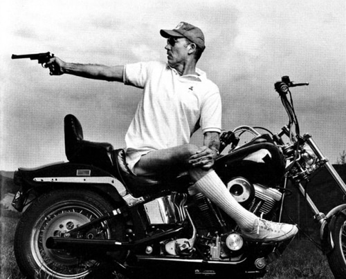 Thompson sitting on motorcycle and pointing the gun.