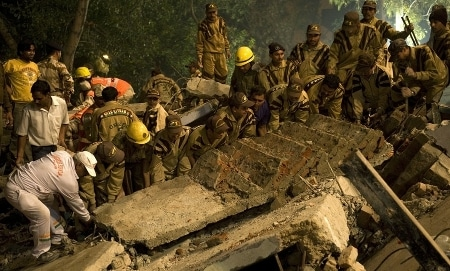 Firefighters rescuers lifting rubble for searching people.