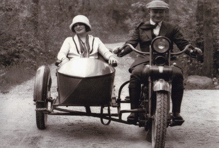 vintage couple riding motorcycle sidecar dirt road