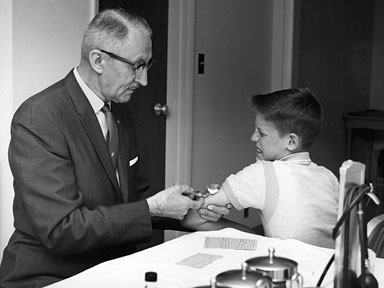 vintage young man getting shot vaccine at doctor's office