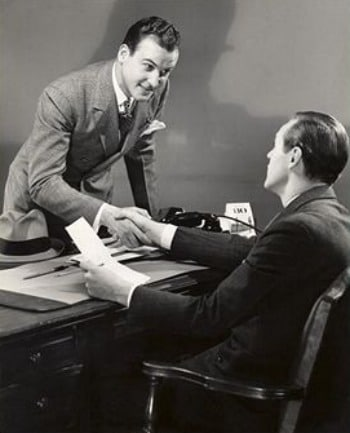vintage businessmen closing deal handshake at desk