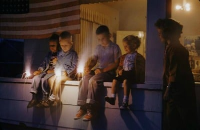 Vintage kids with sparklers in their hands sitting in the porch.
