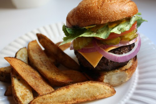 grilled hamburger with french friends on paper plate