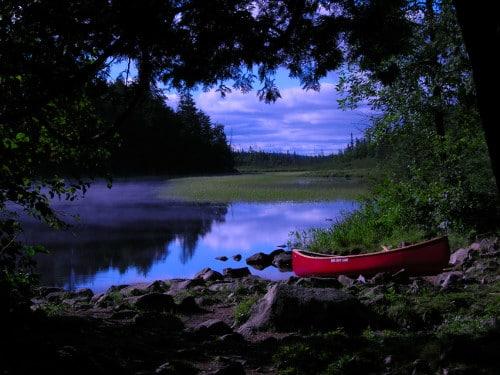 rad canoe next to lake on shore through trees