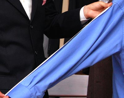 Tailor measuring the arm sleeve of blue dress shirt.