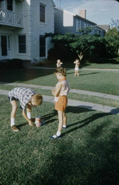 Vintage kids lighting fireworks in the yard.
