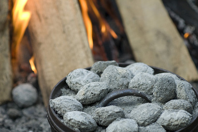 dutch oven coals charcoal near bonfire outdoor cooking