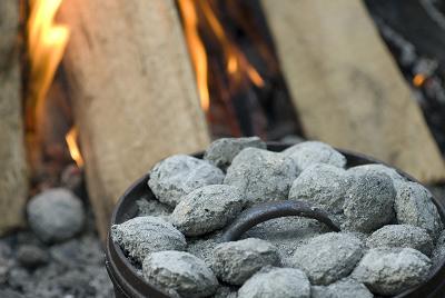 Dutch oven coals charcoal near bonfire outdoor cooking.