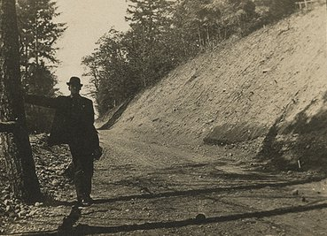 vintage man learning against tree mountain dirt road