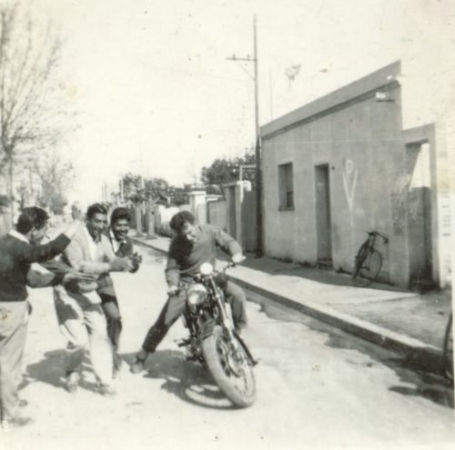 Vintage man learning to ride motorcycle bike tipping.