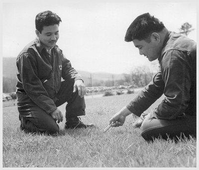 Vintage men playing mumblety-peg pocket knife game.