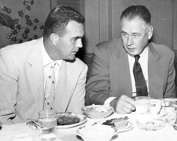 Vintage men in suits eating dinner at table.