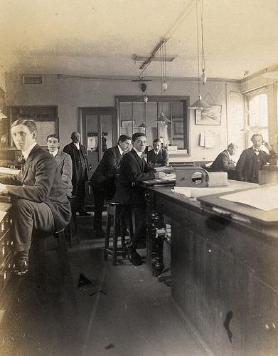 19th century office men standing high stools at desks