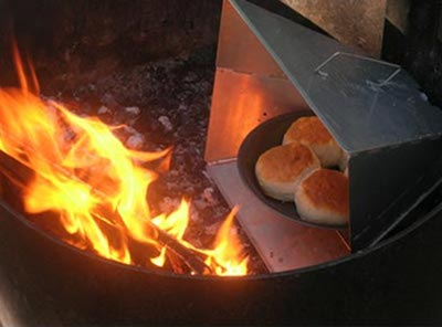 reflector oven next to fire cooking biscuits