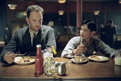 Tom Hanks and a boy eating in a Road to perdition movie.