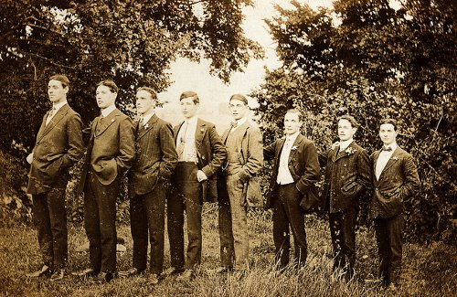 Vintage group of men standing in line sequence of tall to short.