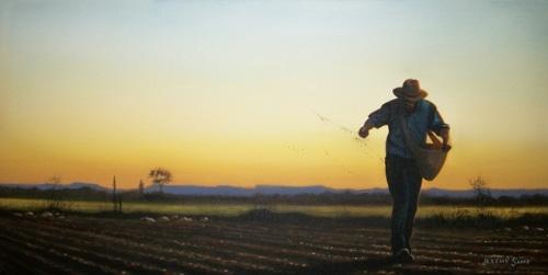 farmer in field planting seeds by hand dusk