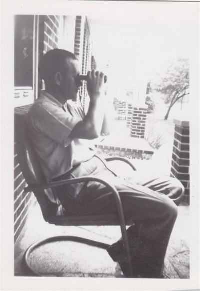man in chair on porch looking through binoculars