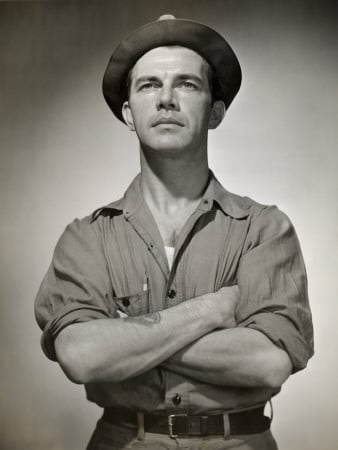 Vintage working class man standing while wearing hat.