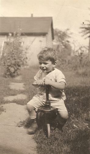 vintage little boy sitting on tricycle toy in yard