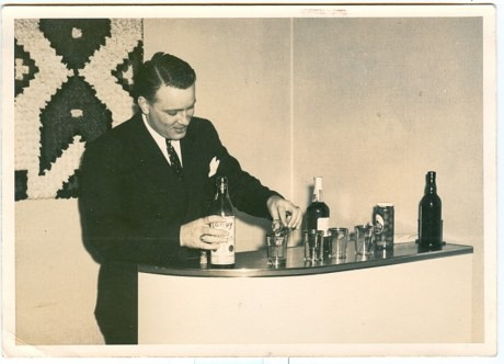 Vintage man serving drinks at home bar.