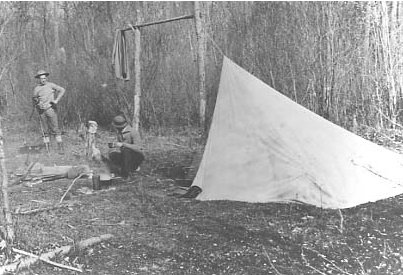 Vintage man camping in woods with tent and campfire.