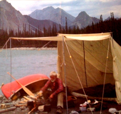 Vintage man camping next to lake with red canoe in the mountains.