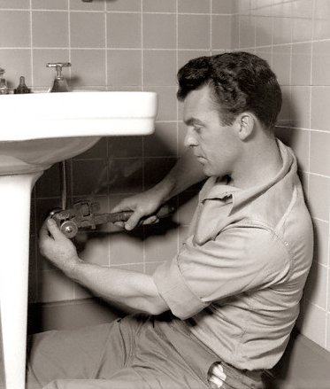 Vintage plumber working on sink sitting on ground.