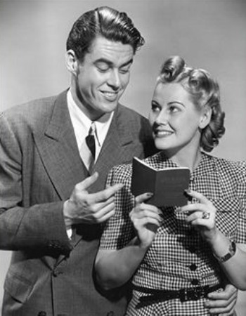 vintage man next to women reading small notebook smiles
