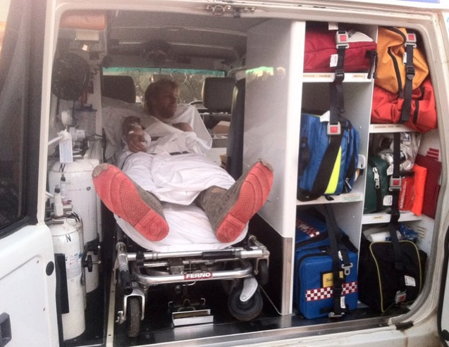 Man in back of ambulance after kangaroo accident.