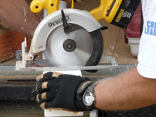 dewalt circular saw in use cutting wood protective gloves