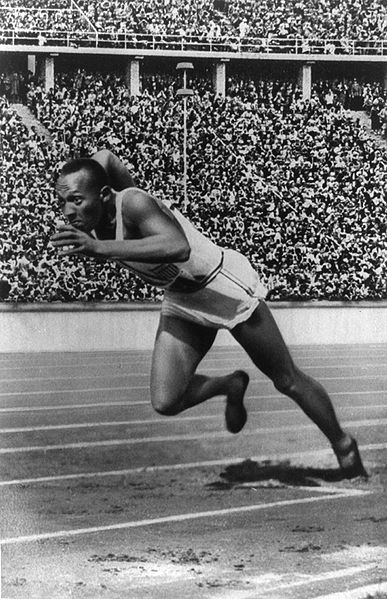 Jesse Owens running in the track field stadium for action shot.